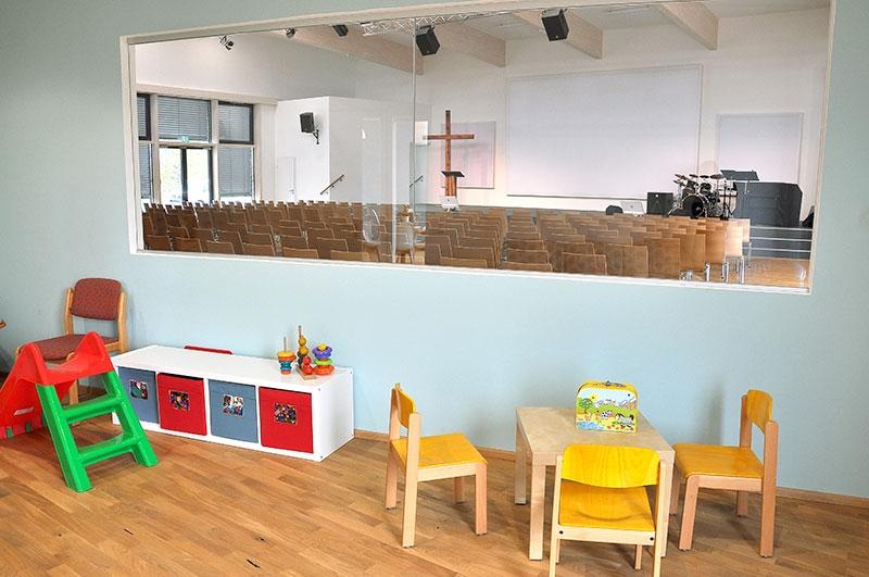 Mutter-Kind-Raum mit Blick in den Gottesdienstsaal